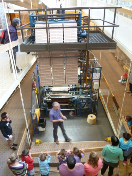 The volunteer explains how the loom works.We are on the second floor looking down.